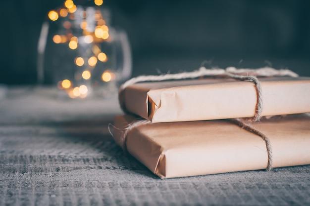 Geschenk zwei oder präsentkarton auf holztisch und defocused weihnachtsbeleuchtung im hintergrund.