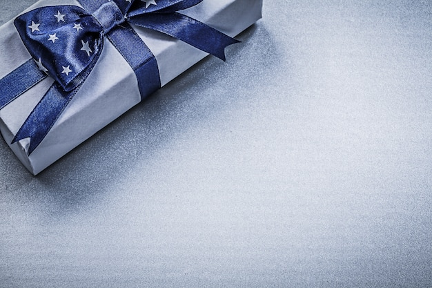 Geschenkbehälter mit bogen auf blauem hintergrundfeiertagskonzept