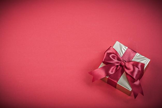 Geschenkbehälter mit gebundenem band auf rotem hintergrundfeiertagskonzept