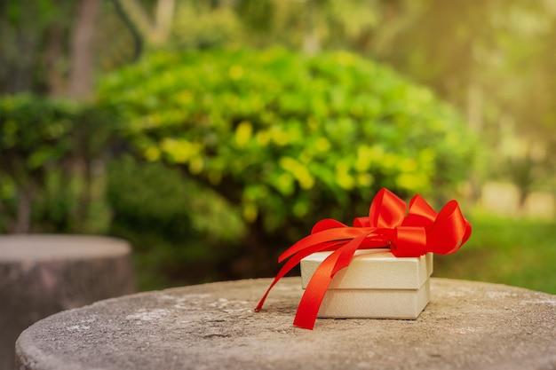 Geschenkbox auf der steinoberfläche im park. geschenk auf dem hintergrund der grünen bäume