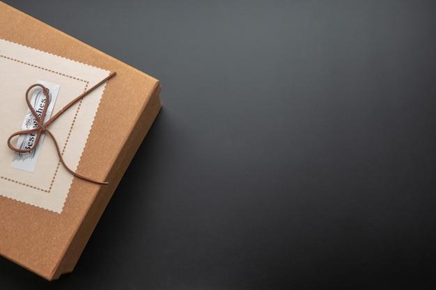 Geschenkbox auf einem dunklen kontrastierenden hintergrund, verziert mit einem strukturierten bogen