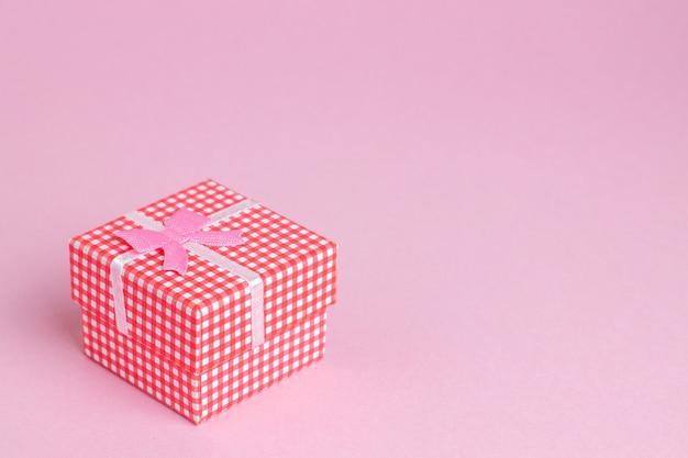 Geschenkbox auf einem rosa hintergrund. die idee für eine postkarte.