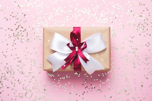 Geschenkbox auf einem rosa hintergrund mit goldenen konfetti-sternen. in einer schachtel in einem bogen präsentieren.