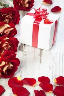 Geschenkbox auf einem weißen brett mit roten rosen