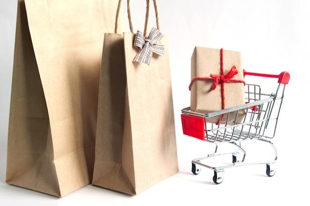 Geschenkbox auf einkaufswagen und einkaufstaschen auf weißem hintergrund
