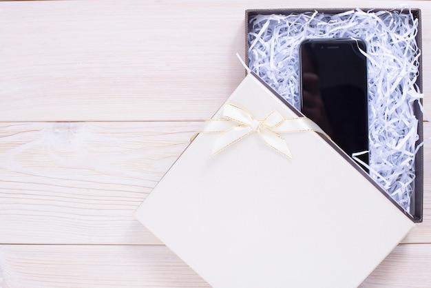 Geschenkbox auf hölzernem hellem hintergrund. mobiltelefon