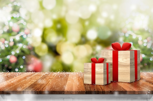 Geschenkbox auf hölzerner plankentischplatte mit abstraktem unschärfenweihnachtsbaumhintergrund mit bokeh licht