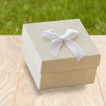 Geschenkbox auf holzbrettern mit grünem naturhintergrund.