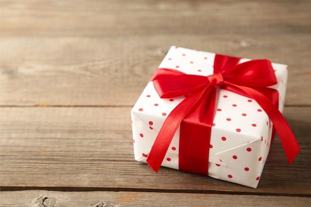 Geschenkbox auf holztisch draufsicht. flache laienkomposition für geburtstag, muttertag oder valentinstag.