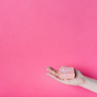 Geschenkbox auf palme hand der frau gegen weißen hintergrund
