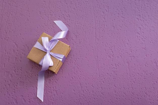 Geschenkbox auf purpurrotem strukturiertem hintergrund.
