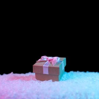 Geschenkbox auf schnee in lebendigen, kräftigen, holografischen farbverläufen