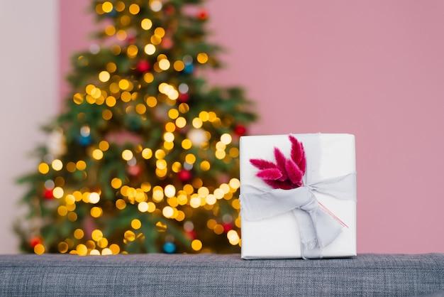 Geschenkbox auf weihnachtsbaumlichtern. kopieren sie platz