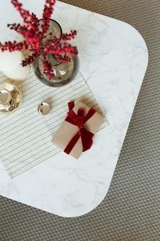 Geschenkbox aus handgeschöpftem papier mit fliege aus rotem band, roten beeren in einer glasvase und dekorationen auf einem marmortisch