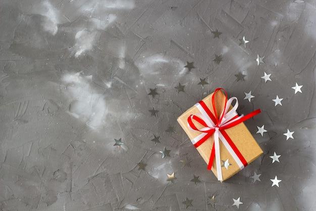 Geschenkbox aus kraftpapier mit schleife und silbernen sterndekorationen auf grauem hintergrund. feierkonzept