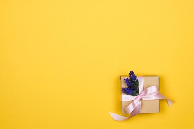 Geschenkbox aus papier mit einer rosa schleife und einem zweig lavendel in der ecke an einer gelben wand
