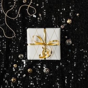 Geschenkbox aus papier mit fliege auf schwarzem funkelndem glitzerhintergrund mit lametta-konfetti. flatlay, draufsicht.