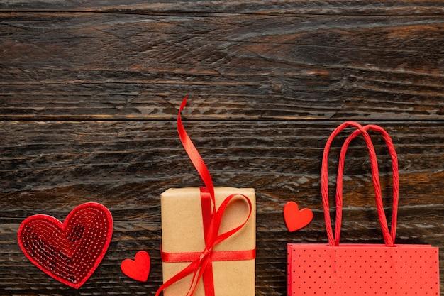 Geschenkbox aus papier mit roter schleife, papiertüte und roten herzen. festliches konzept für valentinstag, muttertag oder geburtstag.