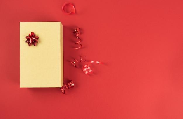 Geschenkbox aus pappe mit banddekorationen auf rotem grund. valentinstag, jubiläum, geburtstag, muttertag, weihnachten.