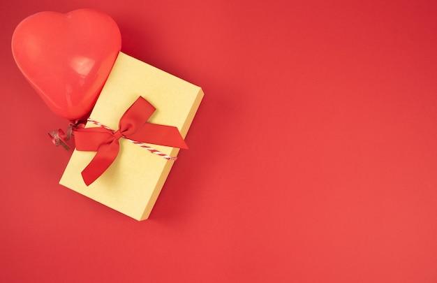 Geschenkbox aus pappe mit banddekorationen auf rotem grund. valentinstag