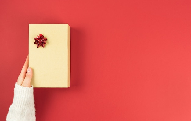 Geschenkbox aus pappe mit dekorationen auf rotem grund. valentinstag