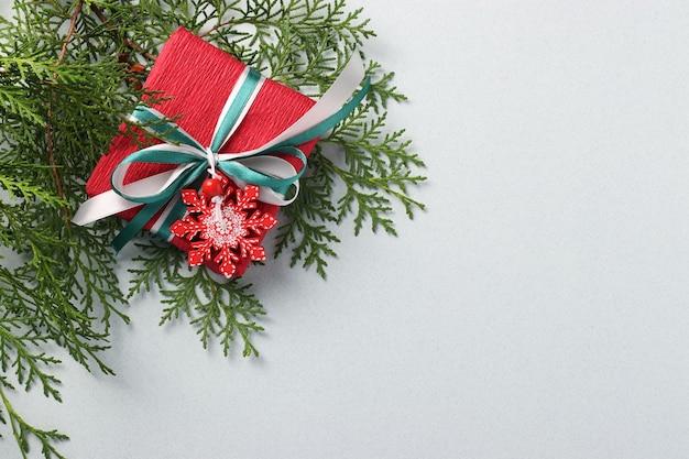 Geschenkbox aus rotem weihnachtspapier mit schneeflocke und bändern auf heller oberfläche.