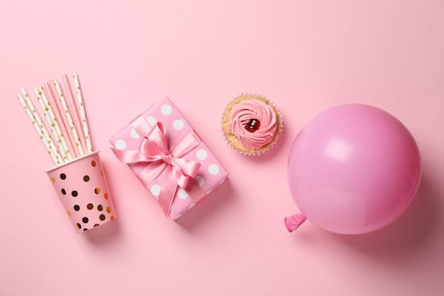 Geschenkbox, ballon, cupcake und pappbecher mit strohhalmen auf rosa hintergrund, draufsicht