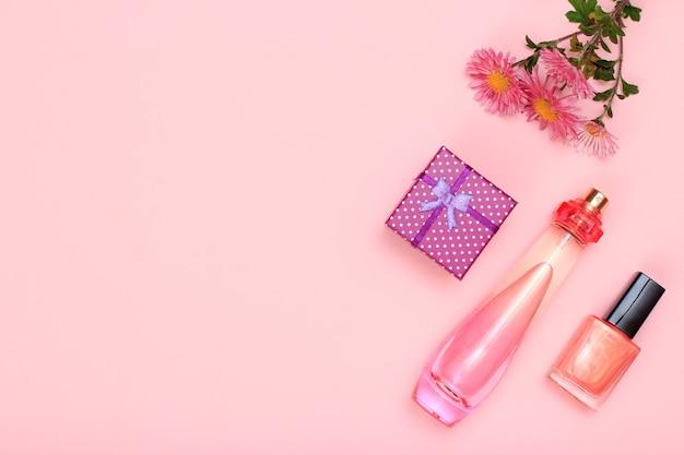 Geschenkbox, blumen, parfümflasche und flasche mit nagellack auf rosafarbenem hintergrund. damenkosmetik und accessoires. ansicht von oben.