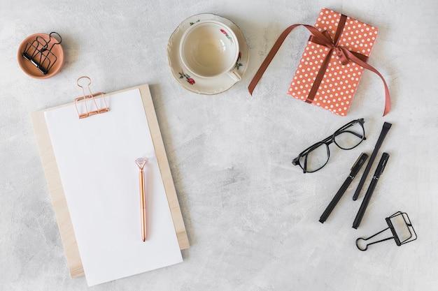 Geschenkbox, brillen, zwischenablage und tasse auf dem teller
