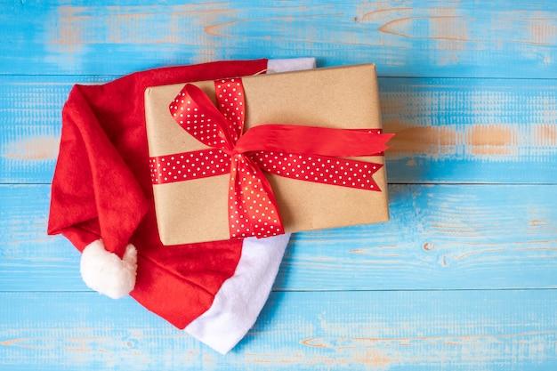 Geschenkbox der frohen weihnachten oder geschenk mit santa claus-hut auf blauem hölzernem hintergrund