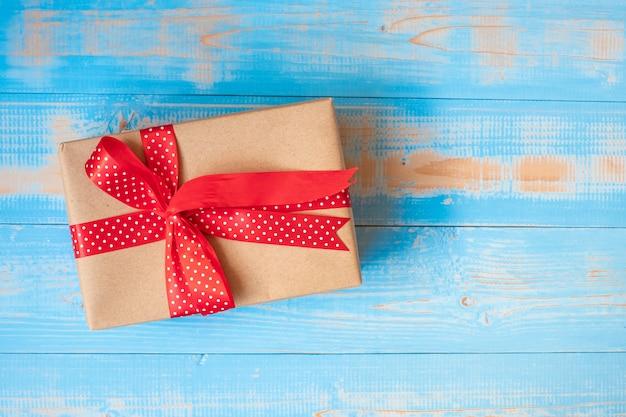 Geschenkbox der frohen weihnachten oder valentine present auf blauem hölzernem hintergrund