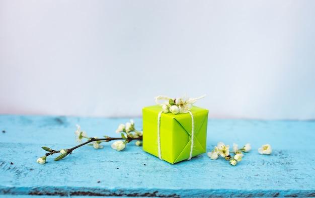 Geschenkbox der hellgrünen farbe auf einem blauen frühlingshintergrund, frühlingsblumen. frühlingszusammensetzung.