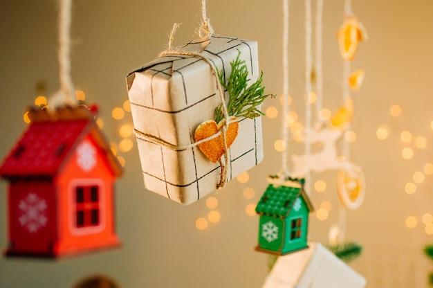 Geschenkbox des weihnachtshandwerkspapierverpackens verziert mit getrockneter zitrusscheibenherzform, die an der schnur auf hellem bokehhintergrund hängt. selektiver fokus auf die geschenkbox.