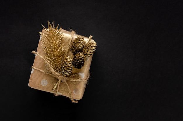 Geschenkbox eingewickelt im kraftpapier mit goldener tanne und kegel auf schwarzem