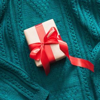 Geschenkbox eingewickelt im kraftpapier mit rotem band auf gestrickter oberfläche.
