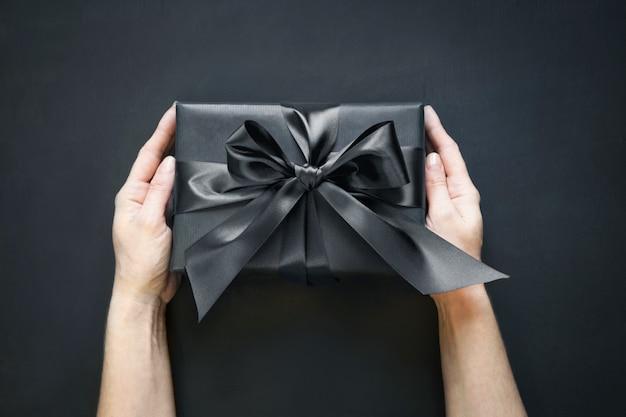 Geschenkbox eingewickelt im schwarzen in der weiblichen hand auf schwarzer oberfläche. ansicht von oben.