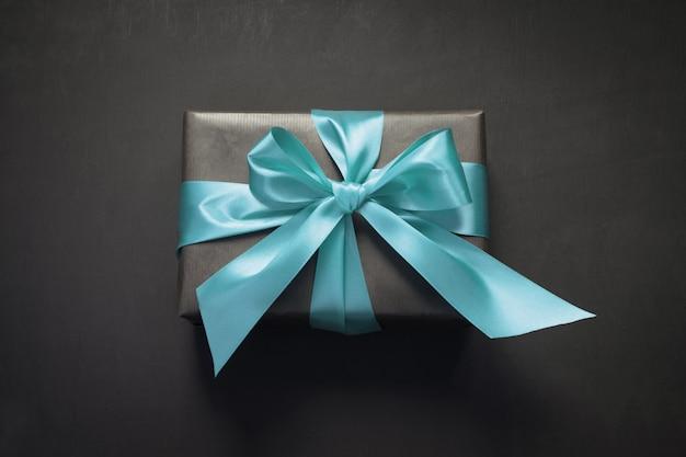 Geschenkbox eingewickelt im schwarzen papier mit rotem band auf schwarzer oberfläche