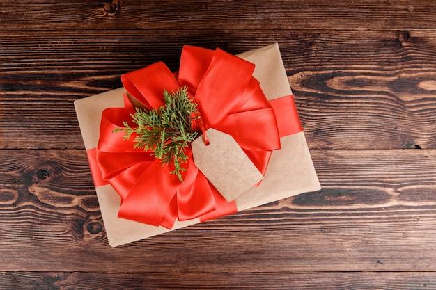 Geschenkbox eingewickelt in recyceltes kraftpapier mit roter schleife und weihnachtskugel auf holz.