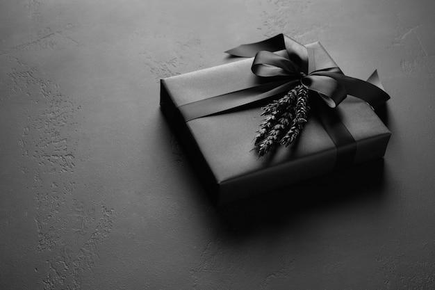 Geschenkbox eingewickelt in schwarzes papier mit silbernem band auf holzoberfläche.
