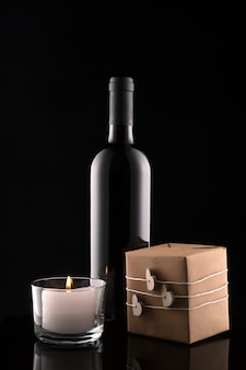 Geschenkbox, flasche wein, kerze auf schwarzem hintergrund. valentinstag. hochzeitstag. romantische grußkarte und einladung.