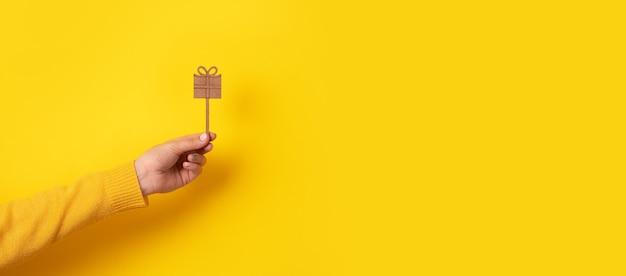 Geschenkbox für urlaub in weiblicher hand über gelbem hintergrund, panoramabild
