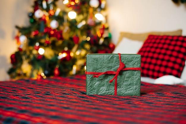 Geschenkbox gebunden mit einem roten band auf dem hintergrund der weihnachtsbeleuchtung mit einem kopienraum