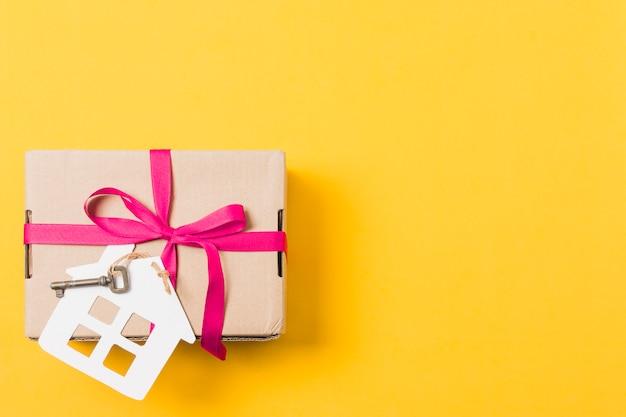 Geschenkbox gebunden mit schlüssel und hausmodell über hellem gelbem hintergrund