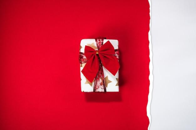 Geschenkbox gewickelt mit rotem band auf zerrissenem rotem papier doppelte rote und weiße farbe flach lag weihnachtskonzept draufsicht