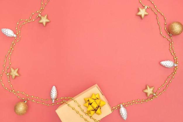 Geschenkbox, goldener stern, glocke und ball auf rosa lebendem korallenrotem hintergrund