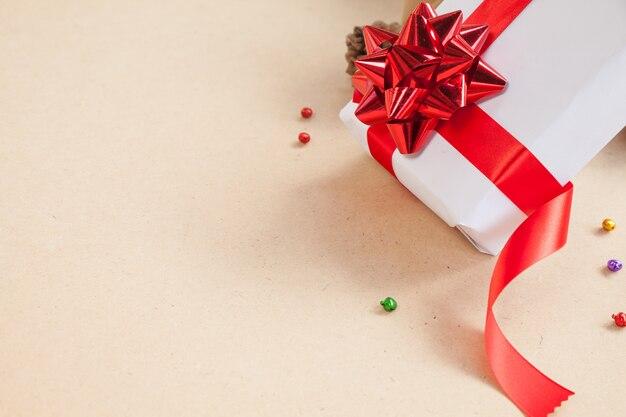 Geschenkbox haben bindung aus rotem band mit dekorationsteilen des weihnachtstages