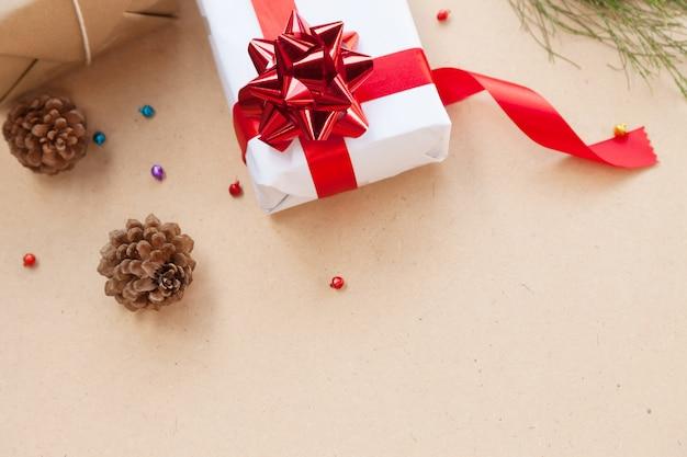 Geschenkbox haben vom roten band mit dekorationseinzelteilen des weihnachtstages und des feiertagstageskonzeptes gebunden. draufsicht copyspace