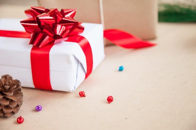 Geschenkbox haben vom roten band mit dekorationseinzelteilen des weihnachtstages und des feiertagstageskonzeptes gebunden