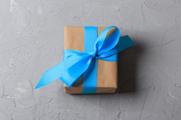 Geschenkbox im kraftpapier auf grauem hintergrund