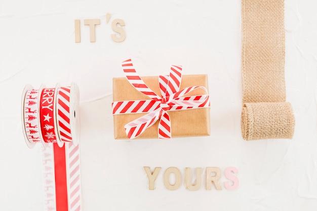 Geschenkbox im kraftpapier mit band nahe elastischer rolle und aufschrift